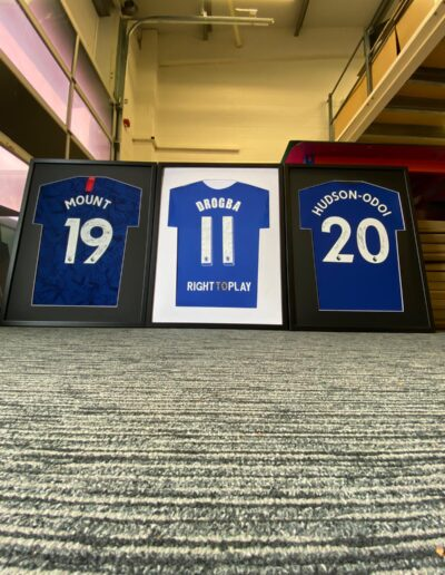 3 football shirts framed up and on display at the TSFS HQ. These shirts are all Chlesea FC shirts. Mount, Drogba and Hudson Odoi